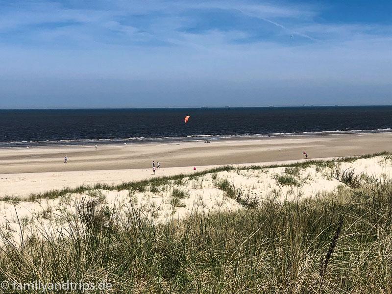 Strand mit Strandsegler in der Ferne auf Spiekeroog.
